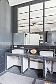 Minimalistisches Bad mit zwei Aufsatzbecken in Loftwohnung mit Industrieverglasung