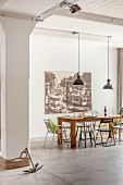 Wooden dining table and various chairs in front of large vintage-style photo