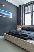 Modern wooden bed and photo art on black wall in minimalist bedroom