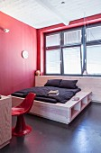 Red minimalist bedroom; custom double bed with elegant storage solution in base below window