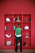 Back view of woman standing in front of red fitted shelving