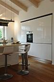Moderne, weiße Hochglanz-Küche mit Holzboden