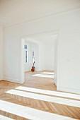 Gitarre lehnt an der Wand in leerer Altbauwohnung