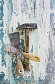 Hammer and spatulas on wooden surface with peeling paint