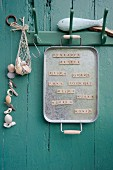 Old metal tray and magnetic scrabble tiles used as shopping list hanging on coat rack
