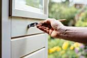 Männerhand streicht eine Gartentür