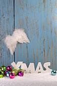 Christmas arrangement of baubles, angel wings and artificial snow in front of wooden wall
