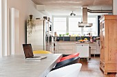 Laptop on concrete table in open-plan kitchen