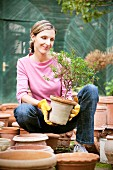 Smiling woman holding potted plant in garden