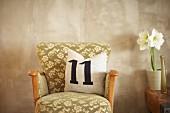 Kissen mit Zahl 11 auf einem Vintage-Sessel