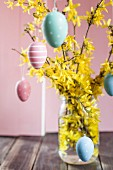 Jar of forsythia decorated with colourful Easter eggs
