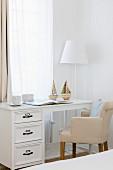 Elegant desk and upholstered chair below window