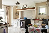 Colourful tablecloth on dining table and black chairs in country-house kitchen