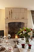 Festlich gedeckter Esstisch mit Blumendeko und Blick auf Kaminfeuer
