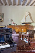 Piano, leather easy chairs and model sailing boat on top of sideboard in living area