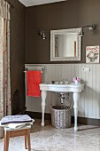 White pedestal sink against wainscoting below mirror with decorated frame in vintage-style bathroom