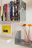 Gerahmter Spruch über weißem Wandboard und Metallboards mit Büchern und Glasvase