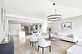 Elegant sofas and armchairs in open-plan interior