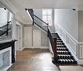 Treppe mit gestreiftem Teppich in Flur mit Zierleisten an den Wänden