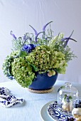 Profiteroles and flower arrangement in blue vase