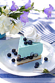 Slice of blueberry mousse tart on table set in blue and white