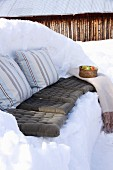 Winter picnic on bench carved out of snow