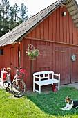 White garden bench below hanging basket outside Falu-red barn