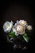 Bouquet of white peonies in silver teacup
