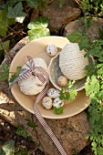 Mit Paketschnur verschnürte Ostereier und Wachteleier auf Teller und in Schale