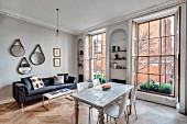 Dining table and sofa in open-plan interior of renovated townhouse apartment