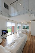 White leather couch, exotic-wood parquet floor and glass balustrade on upper storey in elegant, open-plan interior