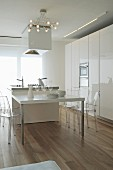 White designer kitchen with extended island counter and plexiglas chairs