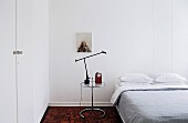 Alarm clock and table lamp on glass table next to double bed in minimalist, white guest room