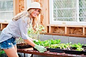 Young woman holding tray of seedlings