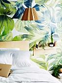 Jungle-patterned wallpaper and bedside shelf in bedroom
