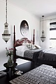 Colonial style bed with carved bed head, pendant lights on both sides in the bedroom