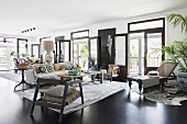 Spacious living room with various seating furniture, French doors and black floor