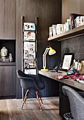 Dunkles Büro mit verkleideter Wand und gelber Schreibtischlampe