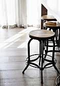 Bar stool in industrial style made of wood and metal on wooden floor
