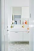 View through open door into the white bathroom with marble floor