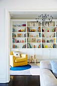 Yellow armchair in front of a shelf with colorful books and toys