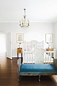 Antikes, weiss gestrichenes Holzbett, davor Rokoko Kleiderbank im Schlafzimmer