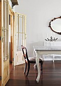 Antique table and chair in front of double doors in dining room with candelabra on dresser below oval mirror on wall