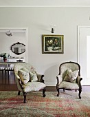 Two antique armchairs with cushions on rug in front of painting and sconce lamp on wall next to open doorway leading to dining room