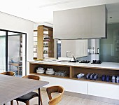 Island counter below extractor hood and open shelves seen past dining table