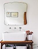 Nostalgisch geschwungener Spiegel über eckigem Waschbecken