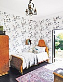 Antique bed in child's bedroom with patterned wallpaper and terrace door