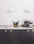 Sconce lamps above black kitchen cupboards with marble worksurface
