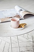 Mug and biscuit on saucer and magazine on white tray table