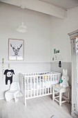 Cot, rabbit toy on stool and classic child's chair in corner of bright room